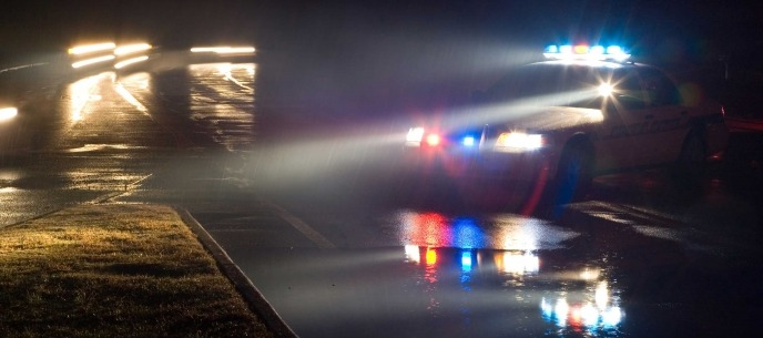 police headlights shining on a road at night
