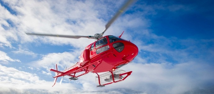 red helicopter flying in the sky